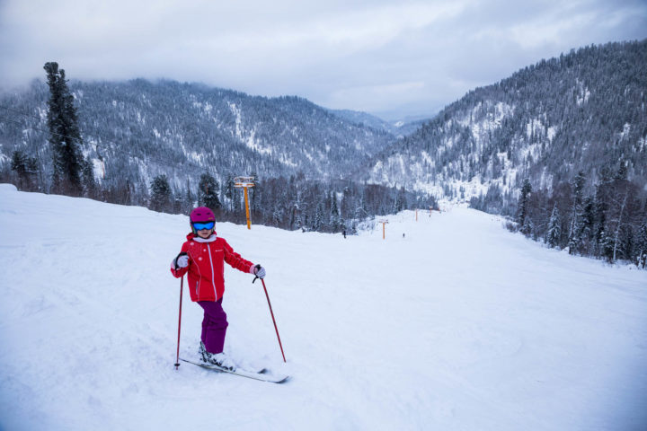 Happy child girl enjoying vacation in winter resort. Little  skiing in mountains. Active sportive toddler wearing helmet learning to ski.  sport for family. Skier racing in snow.
